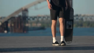Young man with a skateboard. Legs moving in slow-mo. Sport for risky people. Vibe of the youth.