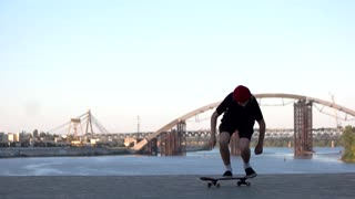 Young man with skateboard. Skater fails to perform trick. Learn on mistakes. Start over again.