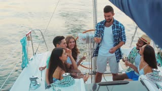 Young people is resting on the sailing yacht. Corporate party on a yacht. Friends spend a weekend on a yacht. Event on the yacht. Merry company is celebrating a birthday on a yacht.