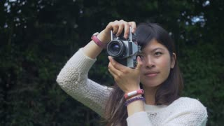 10 Beautiful asian amateur photographer taking photos of people in a park. 4K video