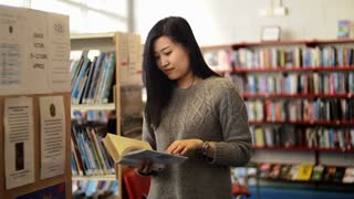 Asian attractive student, doing a research at the library and reading a book