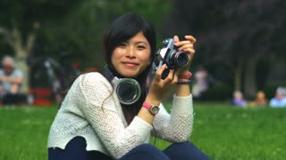 Beautiful asian amateur photographer taking photos of people in a park. 4K video