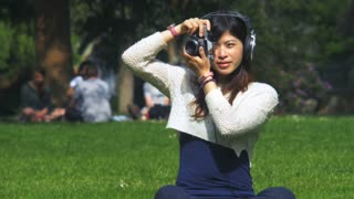 Beautiful asian amateur photographer taking photos of people while listening music. 4K video