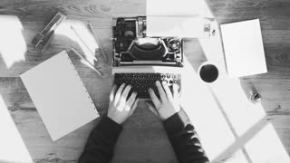 Black and white from above shot of hands typing on a vintage typewriter. space for writing. Film script, more styles in the gallery