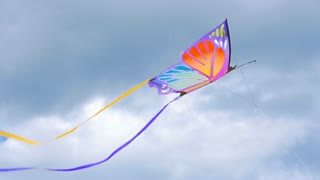 Butterfly kite flying in the air through the clouds, slow motion