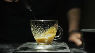 Cream making for cappucino coffee on a transparent cup. Slow motion HD