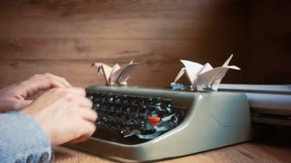 Friend writing a letter with a vintage typewriter, cranes origami on top. Full HD video