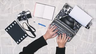 From above shot of hands typing on a vintage typewriter, with an old 35mm film camera, writing a reportage documentary, war notes. Space for writing, Film script, book, letter, newspaper. More styles in the gallery