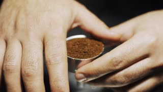 Gently pushing coffee powder into the filter. Traditional italian coffee making. Slow motion