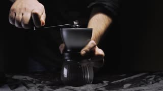 Grinding coffee beans on a hand grinder. Traditional Italian coffee making. Slow motion