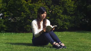 Lovely Asian woman enjoying reading a book in the sunshine at a park. 4K video