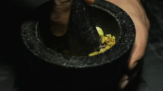 Pistachio grinding on a mortar for cakes and ice screams making. In a studio lighting, slow motion