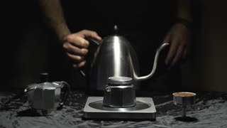 Preparation of Italian traditional coffee, pouring hot water into the filter, slow motion