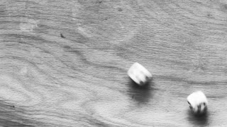 Rolling dice on a wooden board with result 4+6=10. 4K video black and white