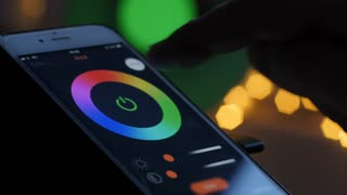 Smart home lighting technology, controlling color of a bulb and scheduling time with a smart phone. Remote controlling light with a phone app. 4k Video