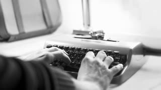 Writing a love letter on an old typewriter from the 1970s. 4K video, black and white