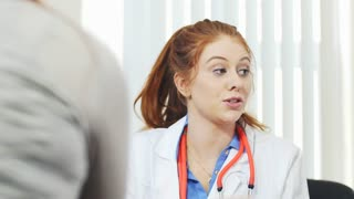 Young and beautiful doctor assisting a patient with a computer screen explaining the issue. 4K video