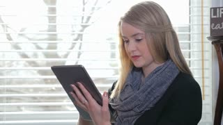 A Young Blonde Female Inside Sitting And Swiping Her iPad Tablet 1