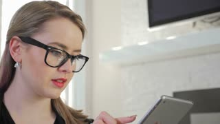 A Young Female Business Entrepreneur Presses And Swipes Across Her iPad Tablet 1