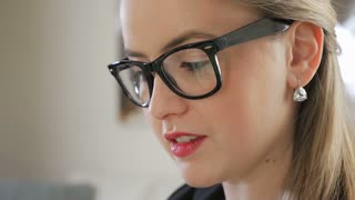 Close Up Of A Young Female Business Entrepreneur With Reflection In Her Glasses Of Her Hand Swiping An iPad Tablet 2