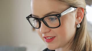 Close Up Of A Young Female Business Entrepreneur With Reflection In Her Glasses Of Her Hand Swiping An iPad Tablet 1
