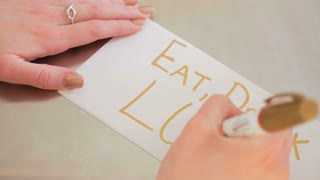 Female Hands Writing Eat Drink Love On A White Piece Of Paper