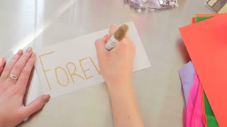 Female Hands Writing Forever On A White Piece Of Paper
