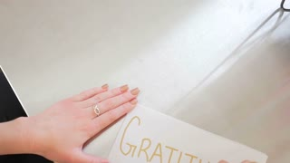 Female Hands Writing Gratitude On A White Piece Of Paper