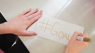 Female Hands Writing Hashtag Goals On A White Piece Of Paper