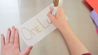 Female Hands Writing One Love On A White Piece Of Paper