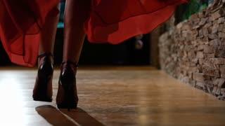 Female model in heels walking on hardwood floor in red dress