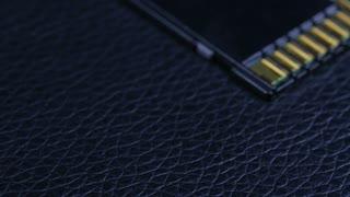 Macro Close Up Of Computer Sd Flash Memory Card Rotating Around