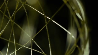 Macro Close Up Of Golden Wireframe Sphere Object Spinning Into Focus