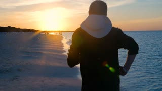 Male Model Running Along A Caribbean Tropical Beach As The Sun Sets