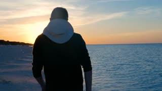 Male Model Walking Along A Caribbean Tropical Beach As The Sun Sets