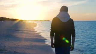 Male Model Walking Along Caribbean Beach At Sun Set