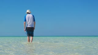 Male Model Walking Out Into Shallow Tropical Water In The Caribbean Ocean 2