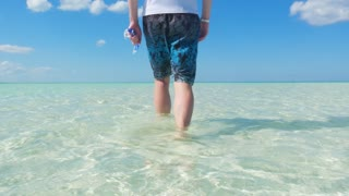 Male Model Walking Out Into Shallow Tropical Water In The Caribbean Ocean