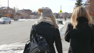 Two Young Females Walking Across The Street Talking In Winter From Behind
