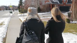 Two Young Females Walking Up To An Intersection Talking In Winter From Behind