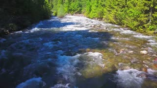 Aerial Drone Close To Water Traveling Along Water Rapids With Mountains And Evergreen Forest 1