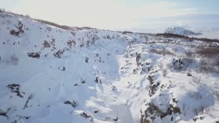 Aerial Drone Flying Above Snow Covered Winter Rock Valley In Iceland 1