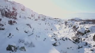 Aerial Drone Flying Above Snow Covered Winter Rock Valley In Iceland 5