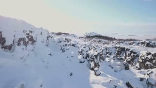 Aerial Drone Flying Above Snow Covered Winter Rock Valley In Iceland 6