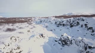 Aerial Drone Flying Above Snow Covered Winter Rock Valley In Iceland 7