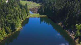 Aerial Drone Footage Of A Lake And Valley With Reflections Of Evergreen Trees On A Mountain 1