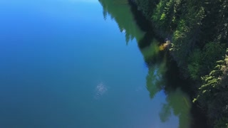 Aerial Drone Footage Of A Lake With Reflections Of Evergreen Trees On A Mountain 1