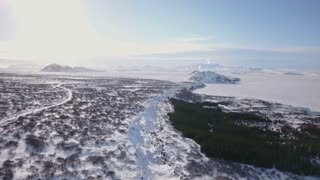 Aerial Drone Tilting Down To Show Snow Covered Winter Rock Valley In Iceland 1