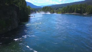 Aerial Drone Traveling Above Flowing Water On Lake With Mountains And Evergreen Trees 1