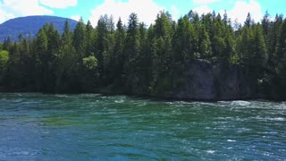 Aerial Drone Traveling Above Flowing Water Towards Cliff And Shoreline 1